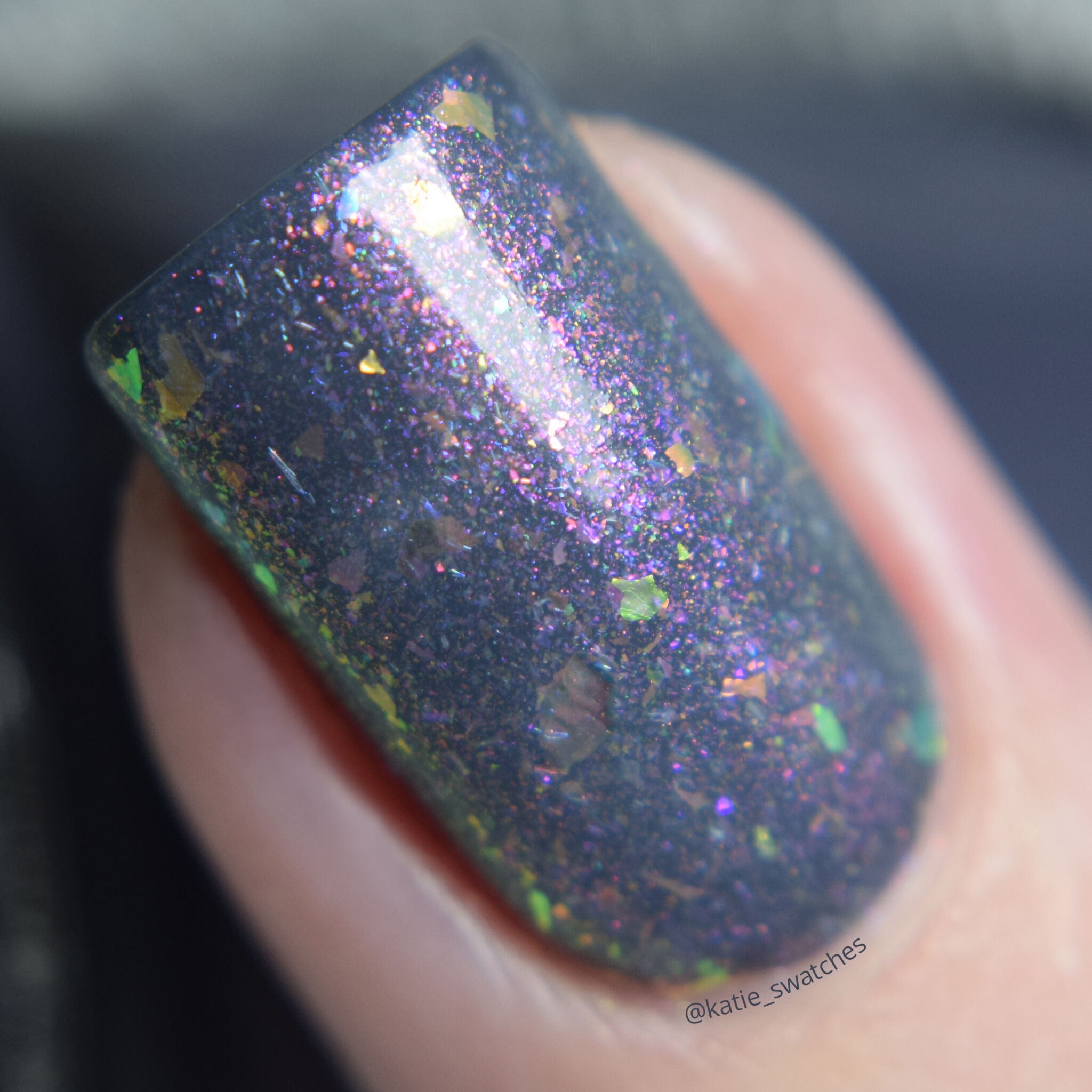 Girly Bits - Thistle While You Work shimmer flakie layered over I'm Pun-decided charcoal creme nail polish swatch macro