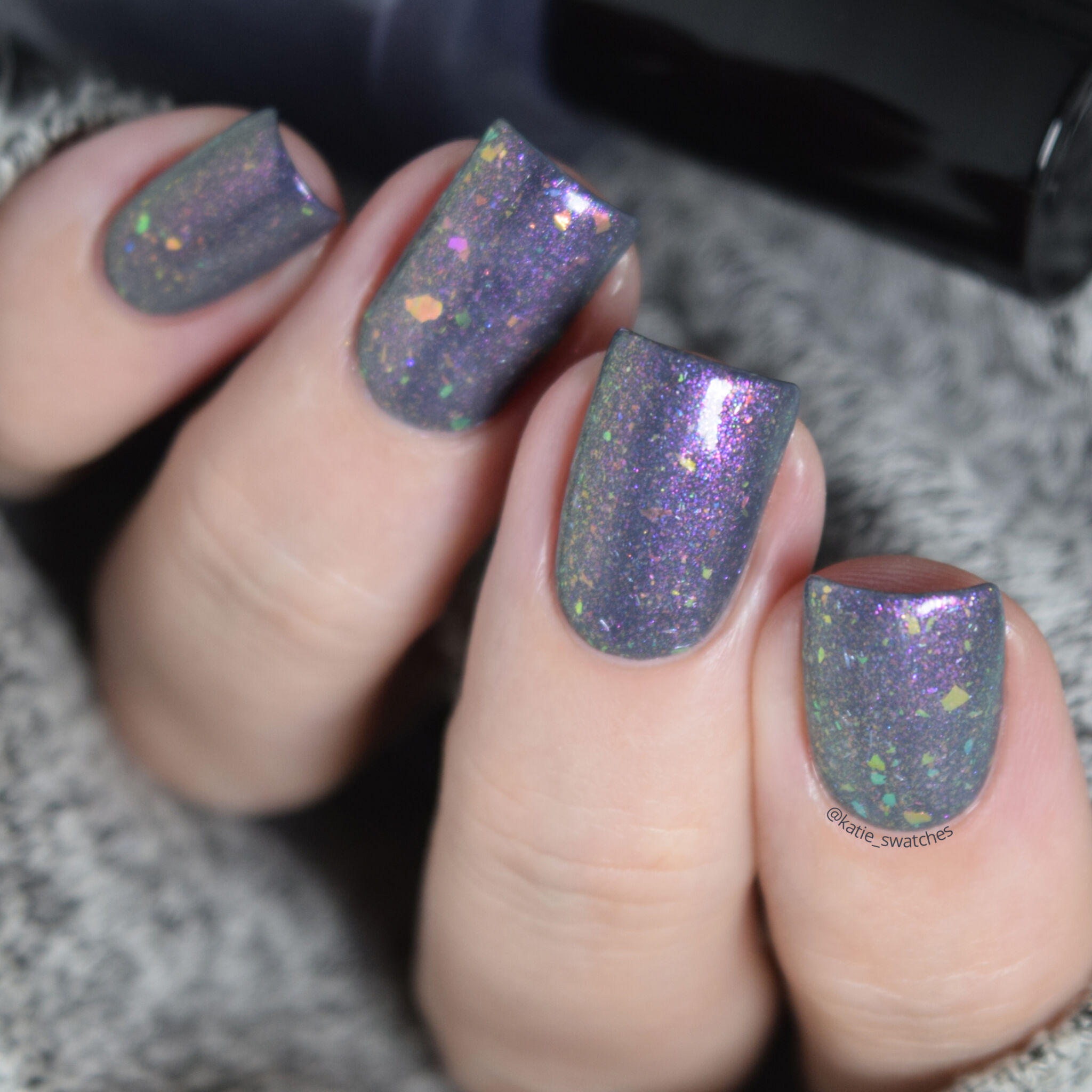 Girly Bits - Thistle While You Work shimmer flakie layered over I'm Pun-decided charcoal creme nail polish swatch