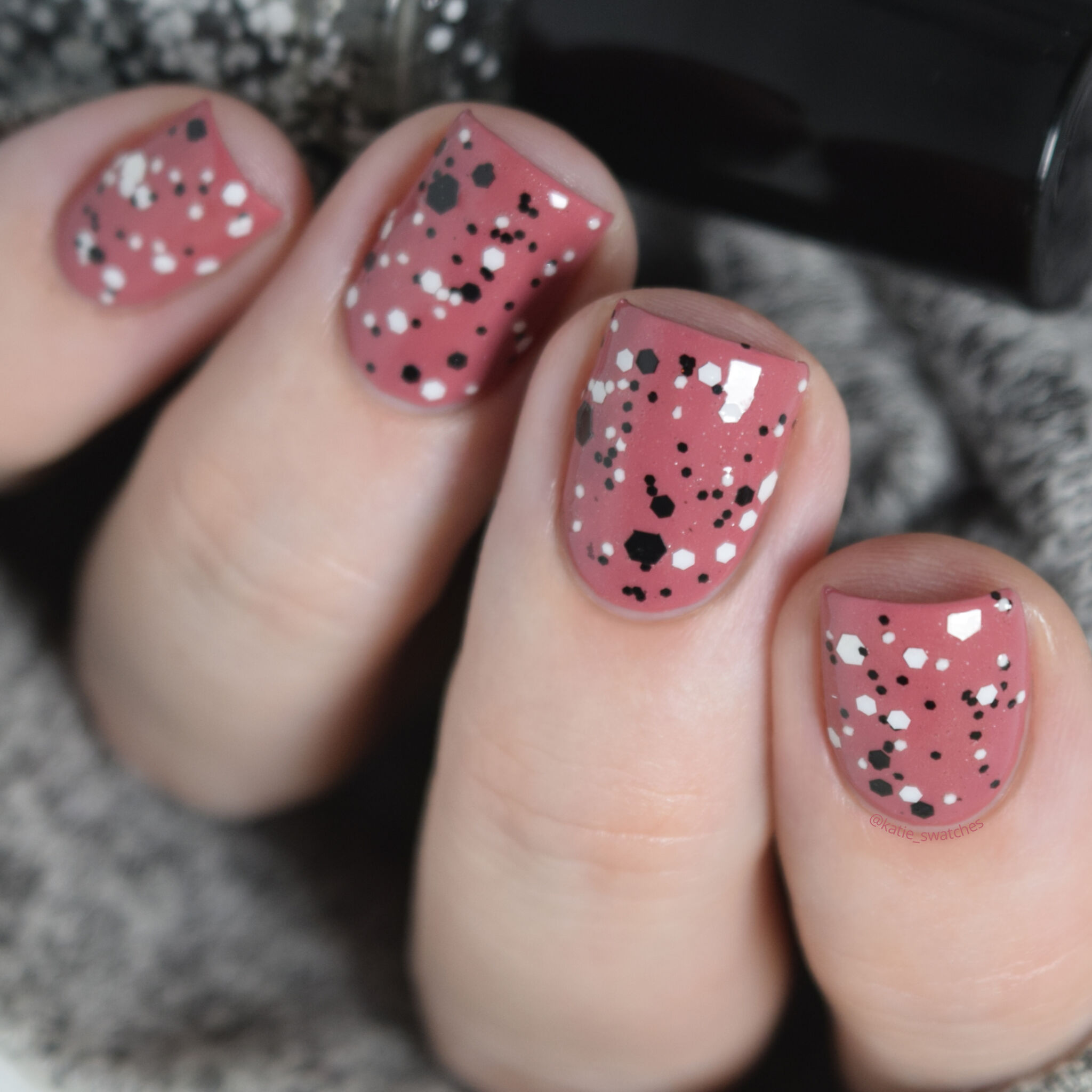 Dollish Polish Putting on the Ritzzz! layered over Sephora Color Hit Rose Bouquet nail polish swatch. Black and white glitter nail polish over a dusty rose creme nail polish.