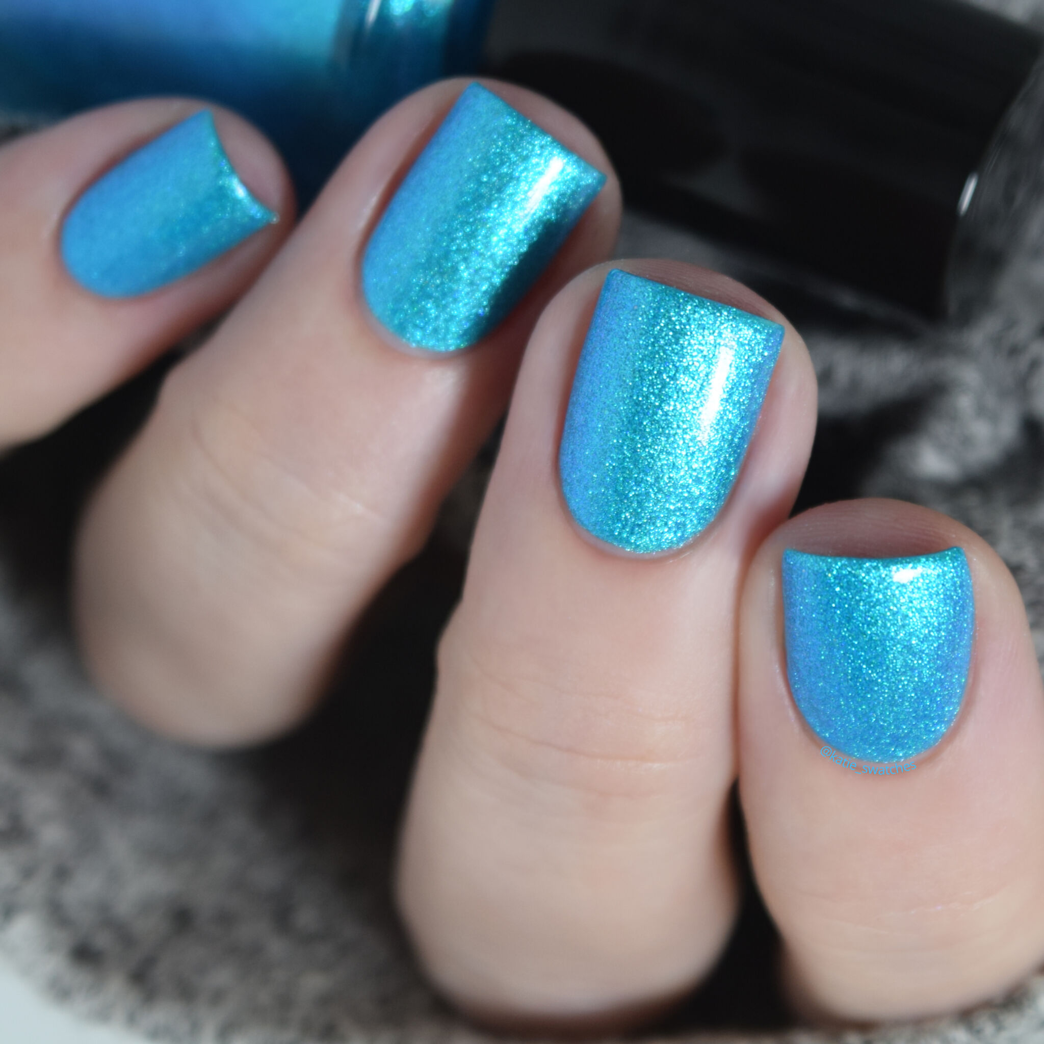 Girly Bits - Lorraine nail polish swatch, with top coat, from the Misheard Lyrics Collection. bright aqua/cyan blue nail polish with a blue/purple shimmer
