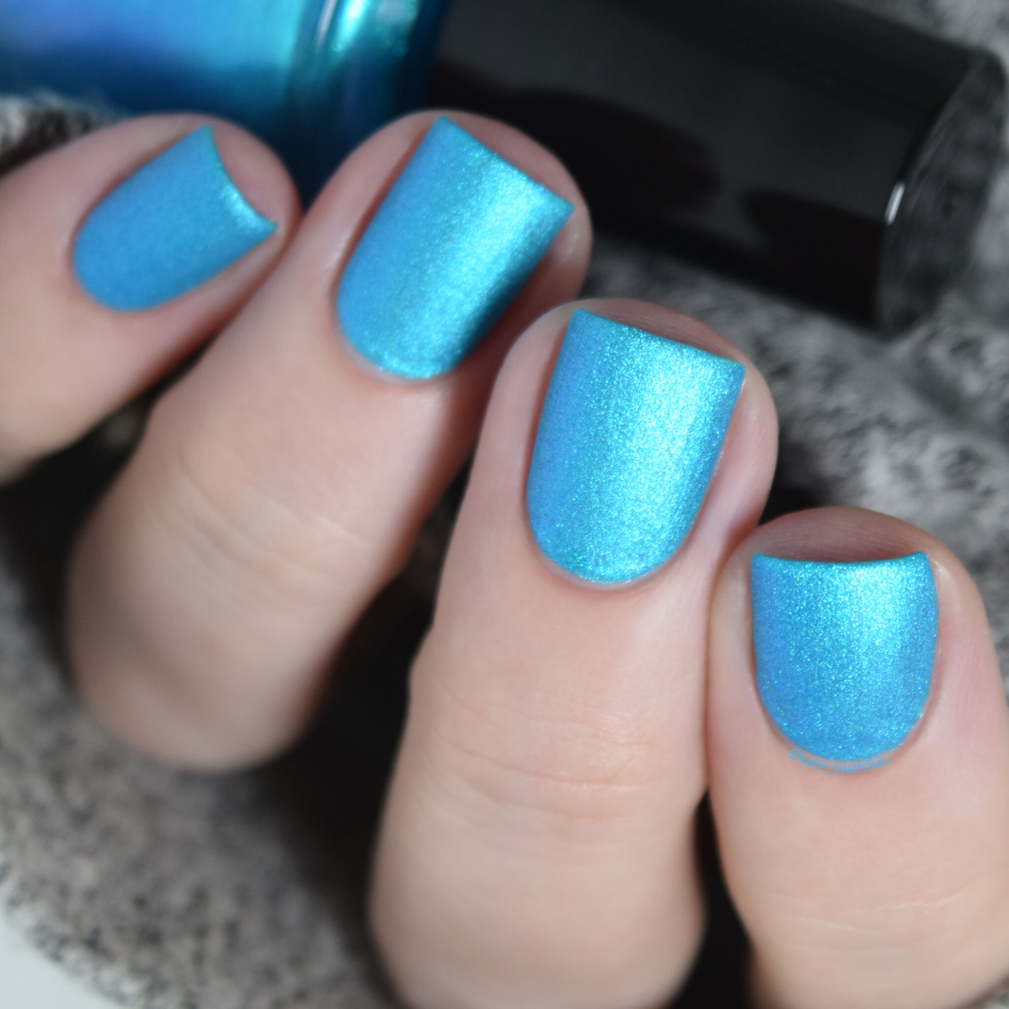 Girly Bits - Lorraine nail polish swatch from the Misheard Lyrics Collection. bright aqua/cyan blue matte nail polish with a blue/purple shimmer